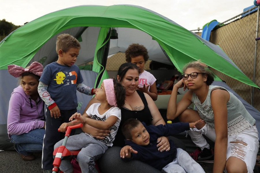 Christine Wade sits among her children at their donated tent in a city-sanctioned encampment:AP Photo