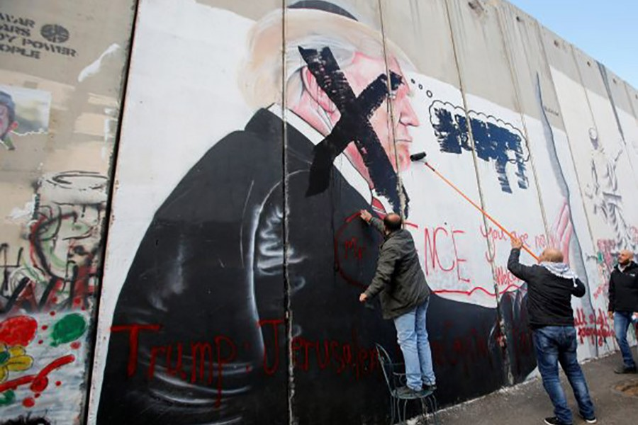 Palestinians damage a mural depicting US President Donald Trump on a part of the Israeli barrier in the West Bank city of Bethlehem on Thursday. - Reuters photo