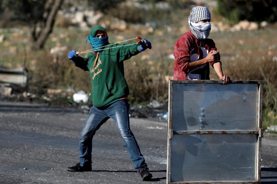 A Palestinian protester is seen using a sling shot to hurl stones towards Israeli troops near the Jewish settlement of Beit El, near the West Bank city of Ramallah. Reuters