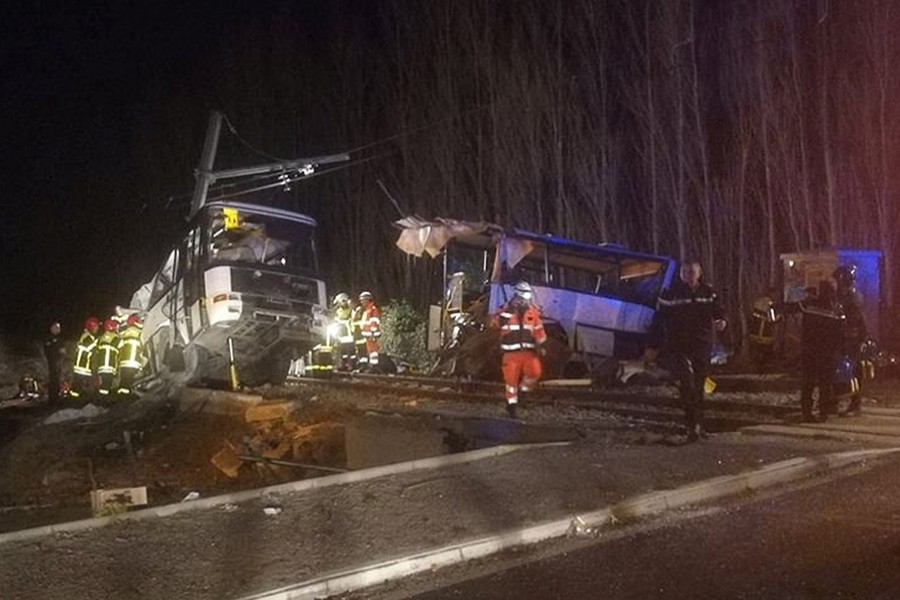 Rescue workers are seen on the site of collision between train and school bus in Millas, France on Thursday. - Reuters