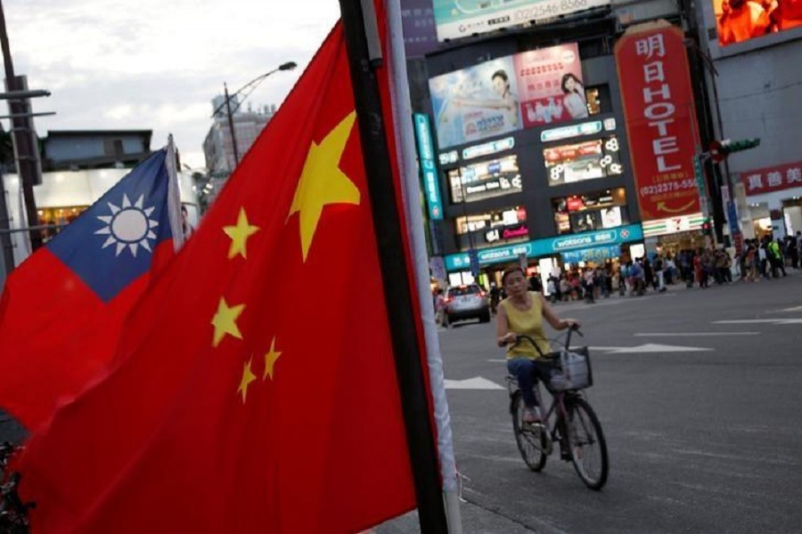 A woman rides a bike past Taiwan and China national flags during a pro-China rally in Taipei, Taiwan, May 14, 2016. Reuters/Files