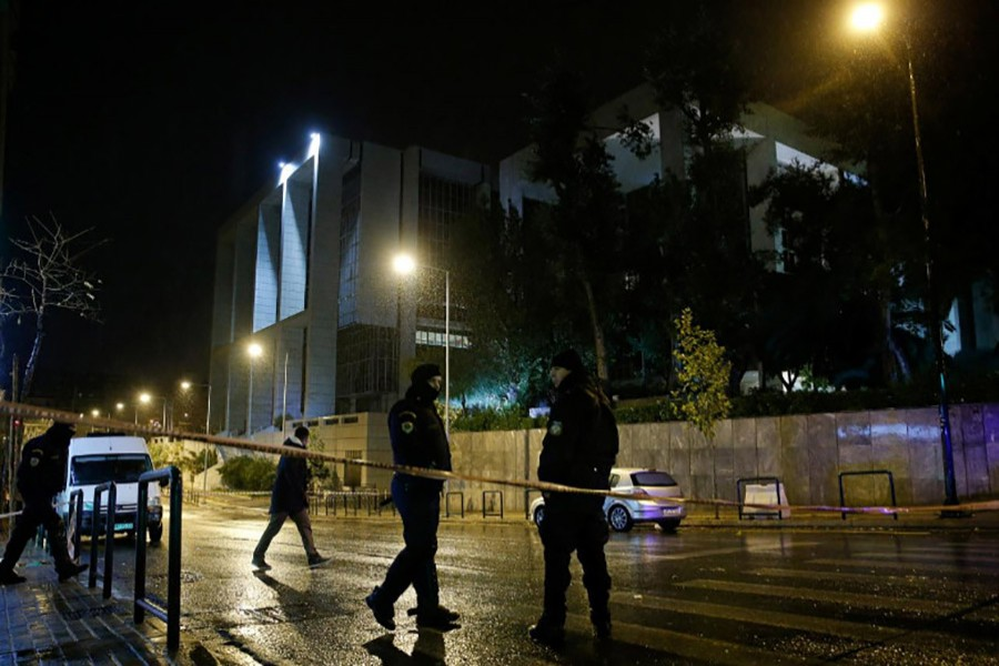 Greek policemen secure the area after a bomb blast at a court building in Athens, Greece on Friday. - Reuters