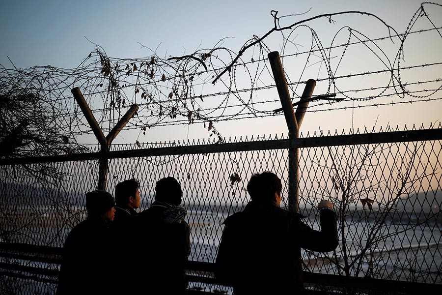 People look toward the north through a barbed-wire fence near the militarised zone separating the two Koreas, in Paju, South Korea on Thursday. - Reuters