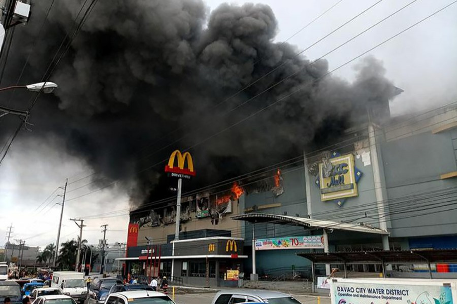 Smoke billows from a shopping mall on fire in Davao City, the Philippines, in this photo obtained from social media. - via Reuters