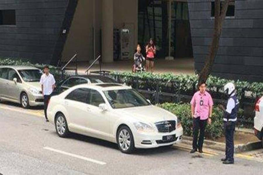 A Land Transport Authority enforcement officer of Singapore conducts his routine patrol along Prinsep Street when he noticed two vehicles belonging to President Halimah Yacob's convoy parked along double yellow lines on Wednesday: Facebook