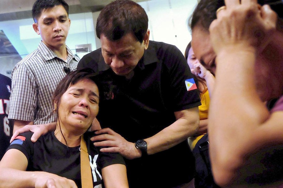President Rodrigo Duterte comforts a family member of a fire victim in Davao city in Philippines on Sunday. -Reuters Photo
