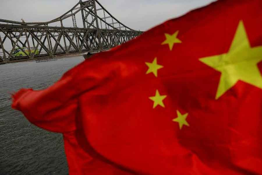 A Chinese flag is seen in front of the Friendship bridge over the Yalu River connecting the North Korean town of Sinuiju and Dandong in China's Liaoning Province on April 1, 2017. -- Reuters photo