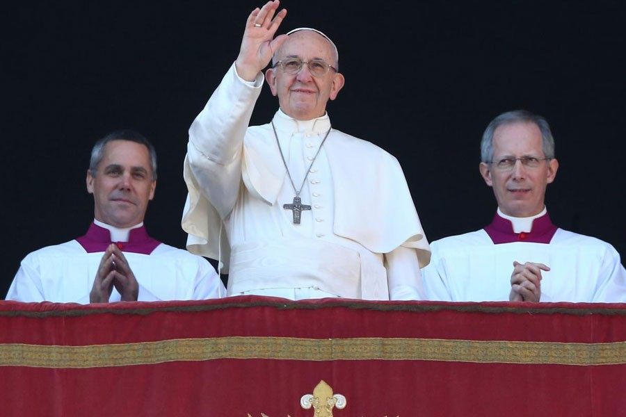 """Pope Francis waves as he leads the """"Urbi et Orbi"""" (to the city and the world) message from the balcony overlooking St. Peter's Square at the Vatican December 25, 2017. (REUTERS)"""