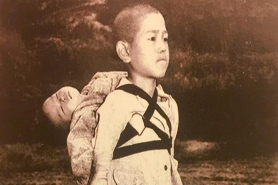 A Japanese child carries the body of his brother.— Internet