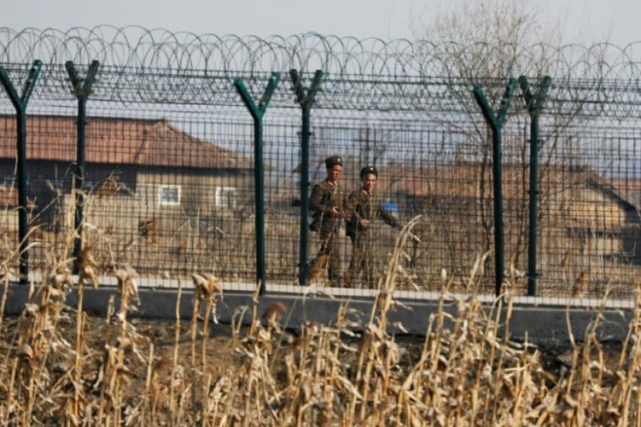 North Korean soldiers patrol behind a border fence near the North Korean town of Sinuiju, March 31, 2017. Reuters.