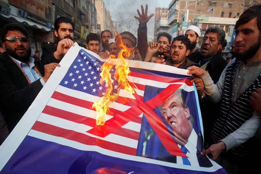 People burn a sign depicting a US flag and a picture of US President Donald Trump as they take part in an anti-US rally in Peshawar, Pakistan, Jan 5, 2018. Reuters