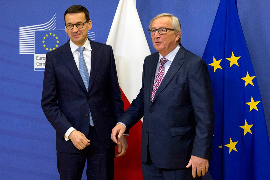 European Commission President Jean-Claude Juncker (right), greets Polish Prime Minister Mateusz Morawiecki prior to a meeting at EU headquarters in Brussels on Tuesday. - AP photo