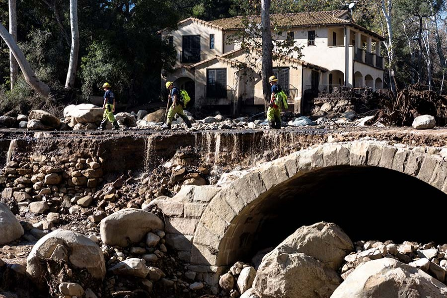 Firefighters walk on a road damaged by mudslides in Montecito, California, US on Wednesday. - Reuters photo