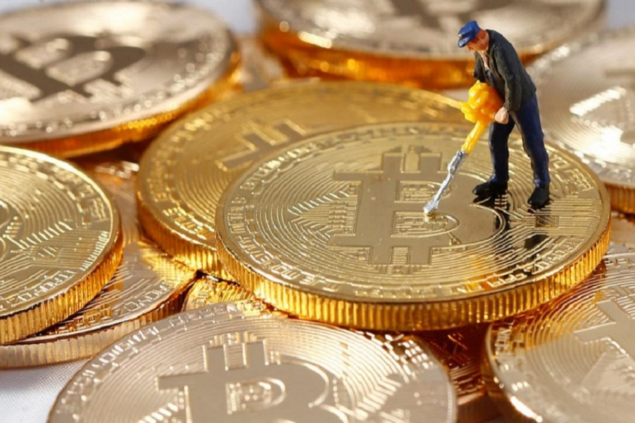 A small toy figure is seen on representations of the Bitcoin virtual currency in this illustration picture, December 26, 2017. Reuters/Files