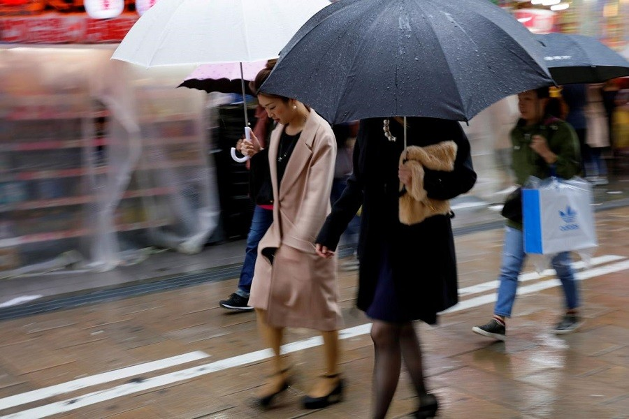 Shoppers walk through the rain in an Osaka shopping district in western Japan October 22, 2017. Reuters