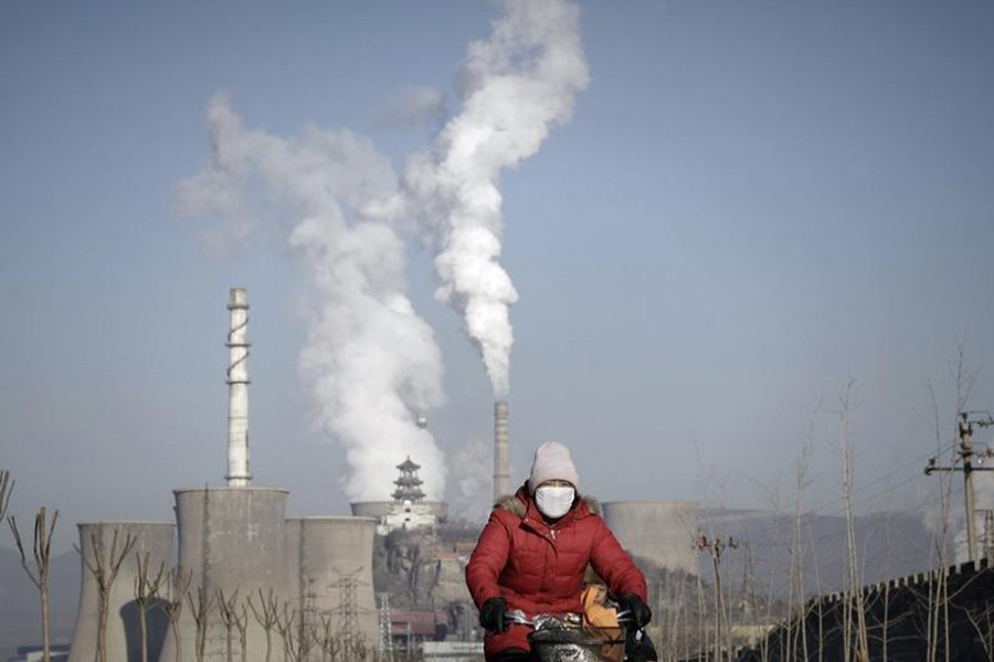 A woman wearing a mask rides past smoking chimneys and cooling towers of a steel plant in Beijing on January 17, 2013. - Reuters file photo