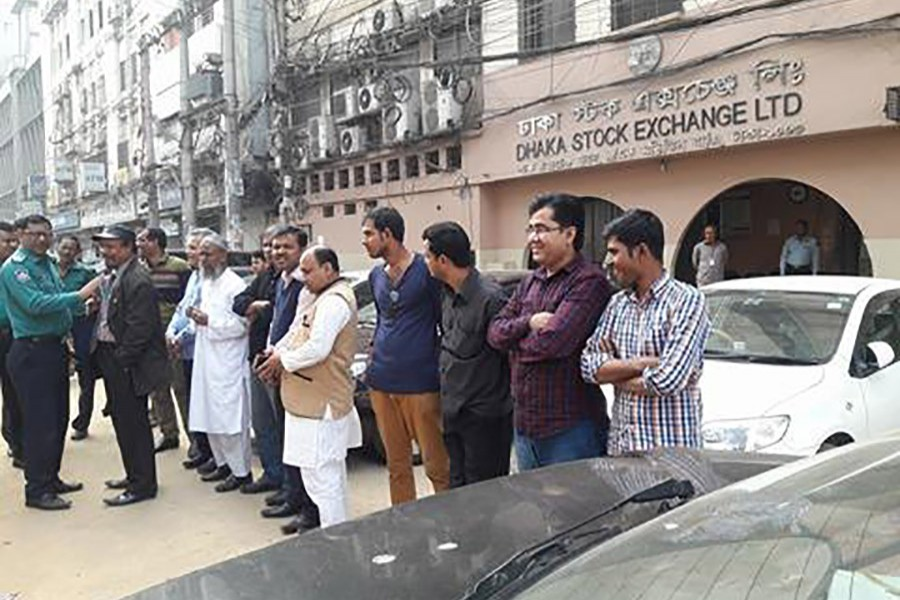 Police are seen calming some small investors trying to stage demonstrations in front of Dhaka Stock Exchange Building on Monday as share prices continue to fall for the five straight sessions. Photo: FE