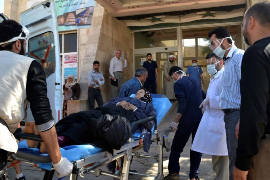A woman affected by what activists say was a gas attack on the town of Telminnes is transferred to Bab al-Hawa hospital, which is close to the Turkish border, to receive treatment April 21, 2014. (REUTERS)