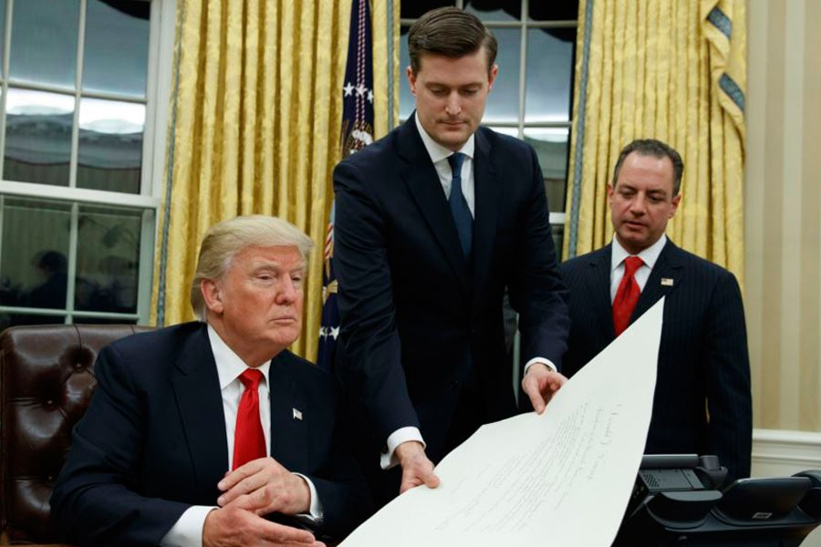 Then-White House Chief of Staff Reince Priebus, right, watches as White House Staff Secretary Rob Porter, centre, hands President Donald Trump a confirmation order in the Oval Office of the White House, in Washington, Jan 20, 2017. (AP)