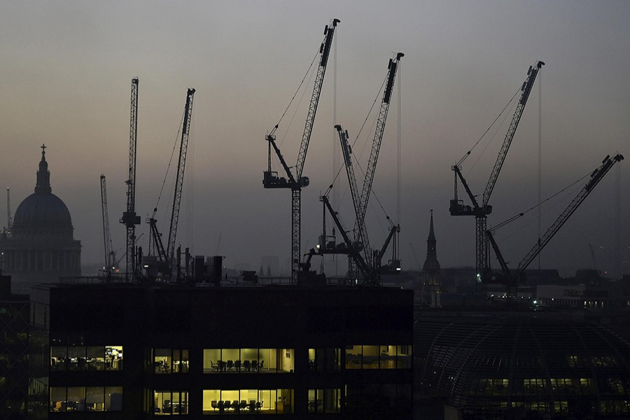 Offices are seen at dusk as St. Paul's cathedral and construction cranes are seen on the skyline in the London, Britain, on Nov 2, 2015. - Reuters file photo