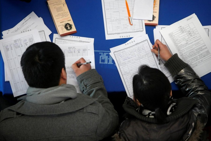 Job seekers fill in application forms during a job fair at Shanghai Stadium February 4, 2012. Reuters/File Photo