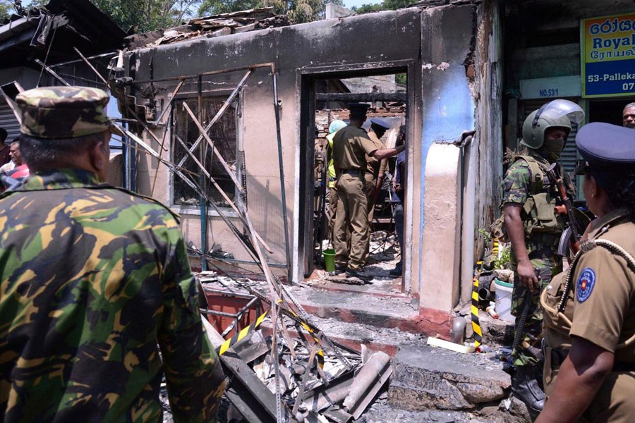 Sri Lanka's Special Task Force and Police officers stand guard near a burnt house after a clash between two communities in Digana, central district of Kandy, Sri Lanka March 6, 2018. Reuters.