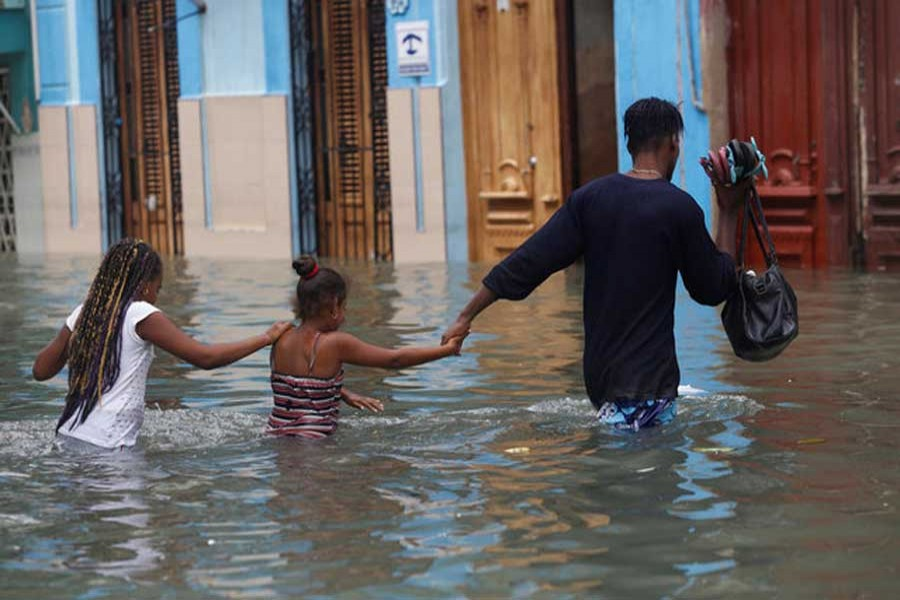 A man and two children wade through a flooded street, after the passing of Hurricane Irma, in Havana, Cuba September 10, 2017. Reuters/File Photo
