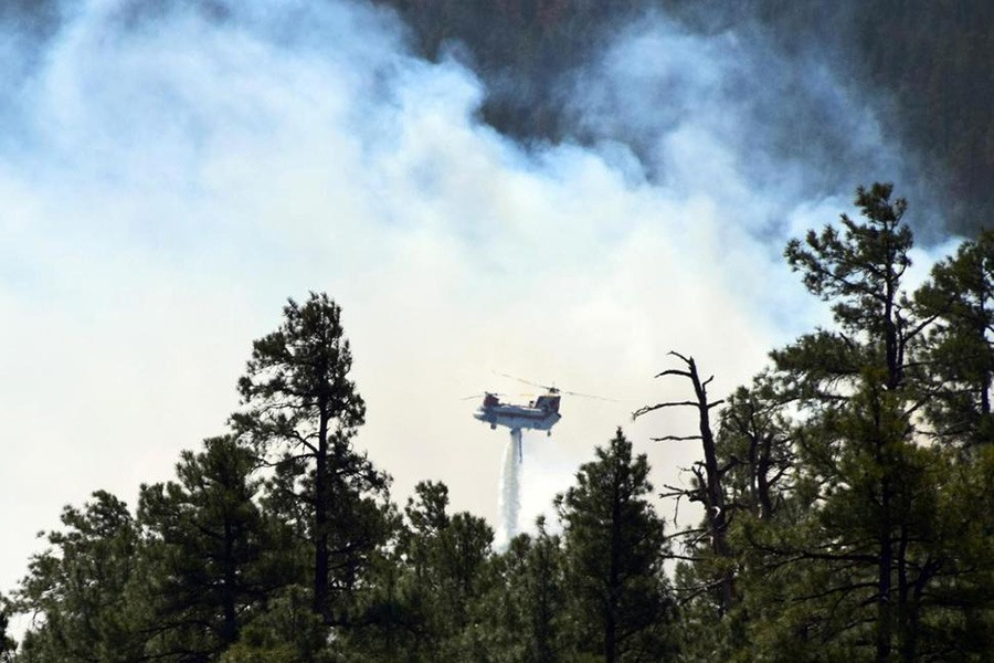 Photo provided by the US Forest Service shows a helicopter fighting a wildfire in north-central Arizona on Monday - via Associated Press
