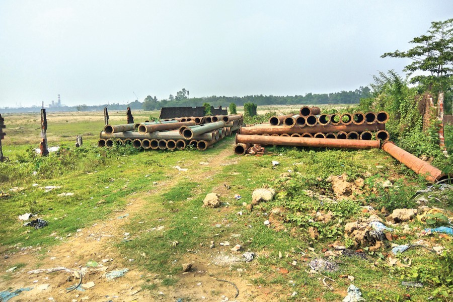 Electricity poles, brought for installation at the Sreehatta Economic Zone (EZ) in Moulvibazar, lying abandoned following legal complications over the EZ — FE Photo