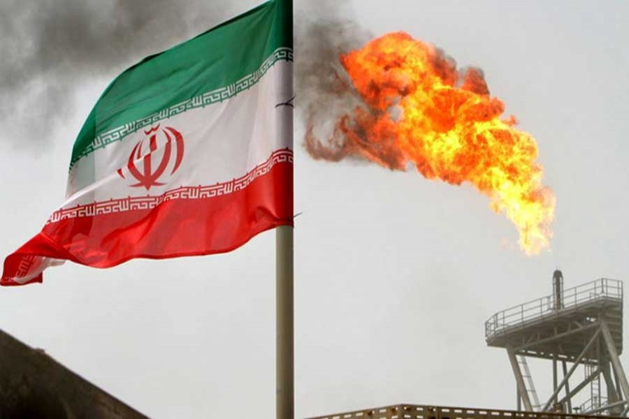 A gas flare on an oil production platform in the Soroush oil fields is seen alongside an Iranian flag in the Persian Gulf, Iran, July 25, 2005. Reuters/File Photo