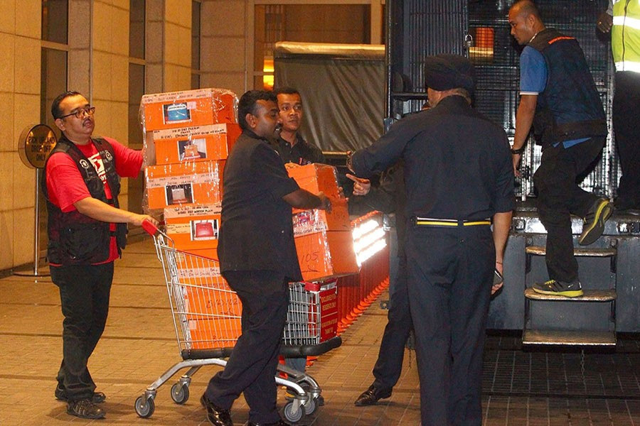 Police prepare to load confiscated items into a truck in Kuala Lumpur, Malaysia on Friday after a raid on a condominium belonging to former Prime Minister Najib Razak - AP photo