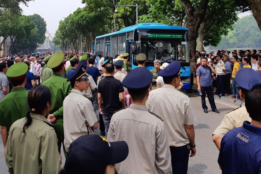 Police stand around a bus after they detained protesters during a demonstration against a draft law on the Special Economic Zone in Hanoi, Vietnam June 10, 2018. Reuters.