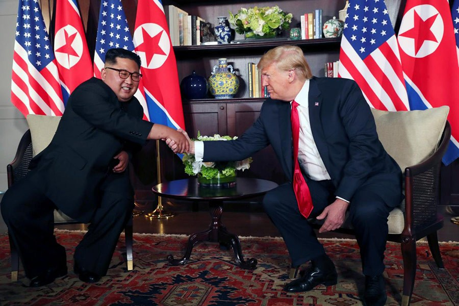 US President Donald Trump shakes hands with North Korea's leader Kim Jong Un before their bilateral meeting at the Capella Hotel on Sentosa island in Singapore on Tuesday - Reuters photo