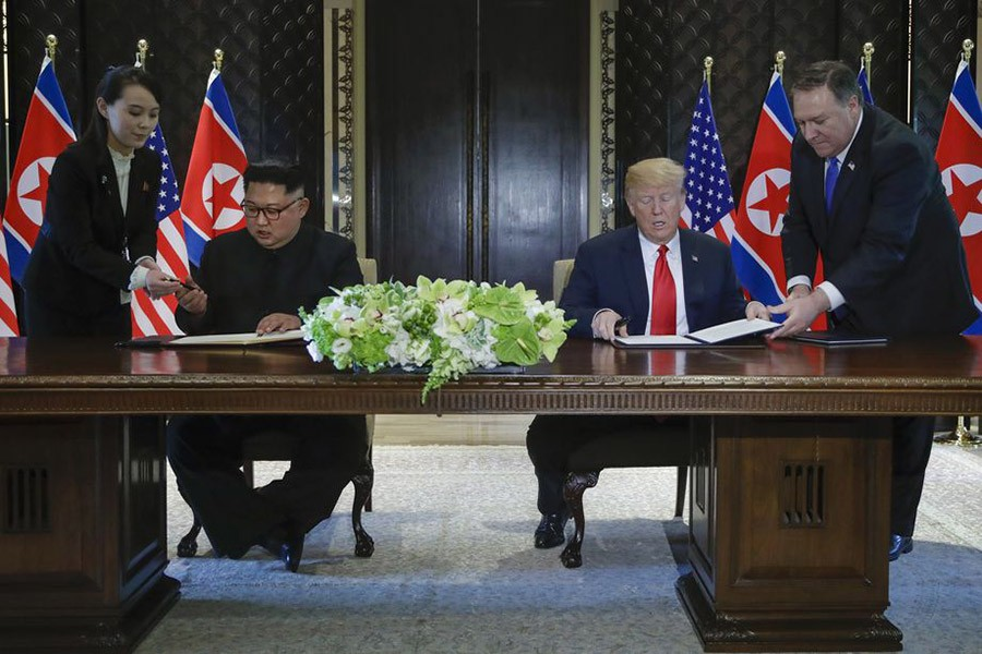 US President Donald Trump and North Korean leader Kim Jong Un prepare to sign a document at a ceremony marking the end of their historic nuclear summit at the Capella hotel on Singapore's Sentosa island on Tuesday - AP photo
