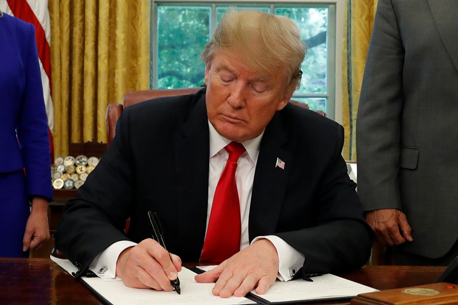 US President Donald Trump signs an executive order on immigration policy in the Oval Office of the White House in Washington, US on Wednesday - Reuters photo