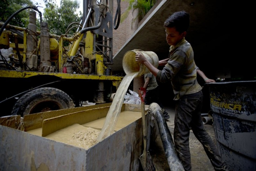 In this file photo, a worker clears the mud from a drill as a water well is put in at a luxury apartment complex in the Campo Alegre neighbourhood of Caracas, Venezuela. - AP photo