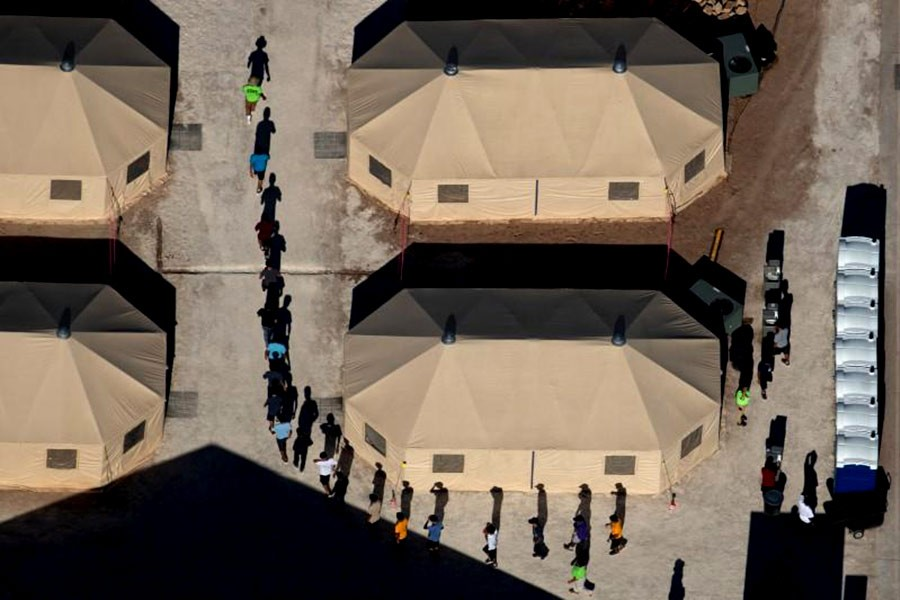 Immigrant children are led by staff in single file between tents at a detention facility next to the Mexican border in Tornillo of Texas in US recently. -Reuters Photo