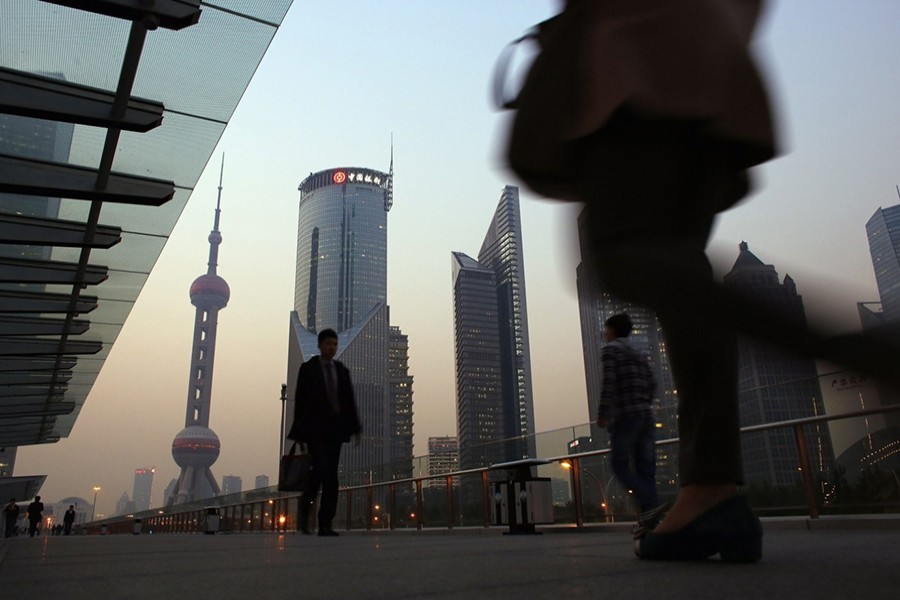 People walk along an elevated walkway at the Pudong financial district in Shanghai - Reuters file photo
