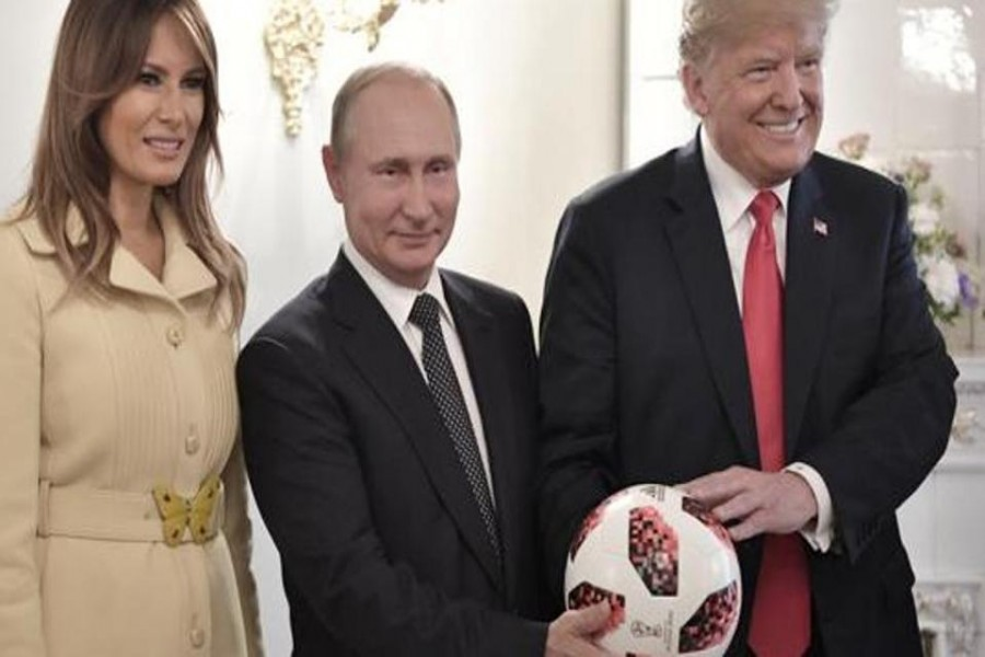 US First Lady Melania Trump, left, Russian President Vladimir Putin, center, and US President Donald Trump, pose with a soccer ball after a press conference following their meeting at the Presidential Palace in Helsinki, Finland, Monday, July 16, 2018. - AP