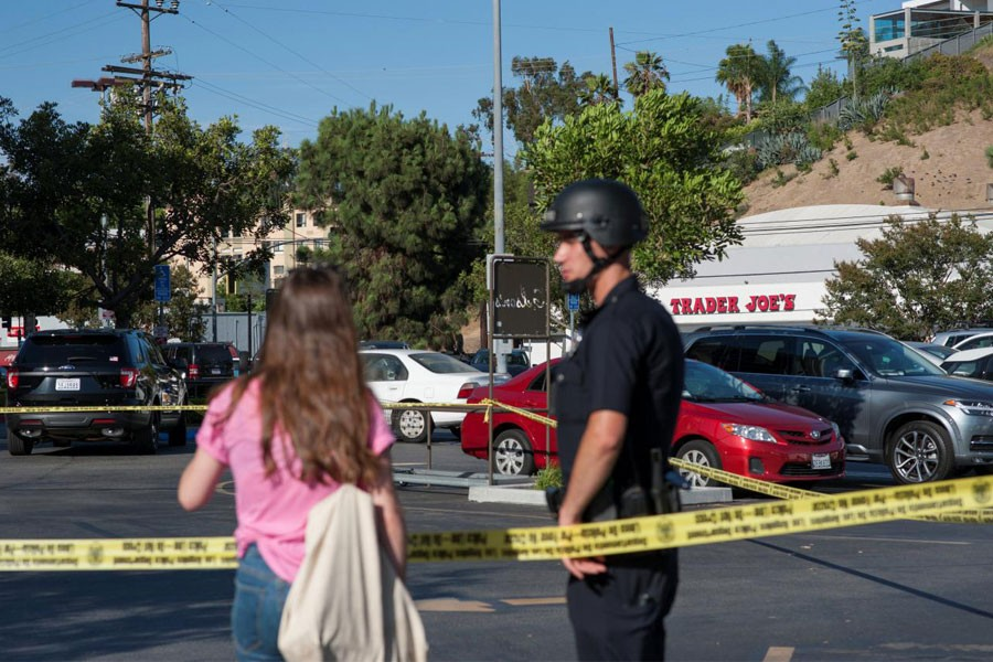 A police officer talks with a woman in a parking lot across the street from a Trader Joe's store where a hostage situation unfolded in Los Angeles, California, Saturday July 21, 2018 – Reuters