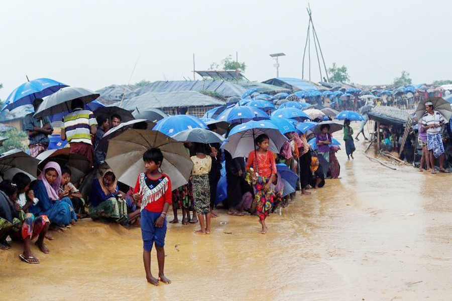 Rohingya refugees queue in the rain to receive food at Kotupalang refugee camp near Cox's Bazar recently— Reuters