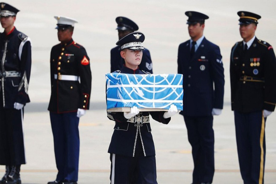 A soldier carrying a casket containing the remains of a US soldier killed during the 1950-53 Korean War, after arriving from North Korea at Osan Air Base in Pyeongtaek on Friday— AFP