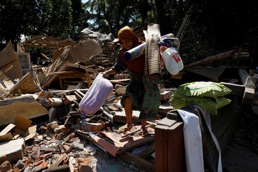 A woman carries valuable goods from the ruins of her house at Kayangan district after earthquake hit on Sunday in North Lombok, Indonesia, August 7, 2018 – Reuters