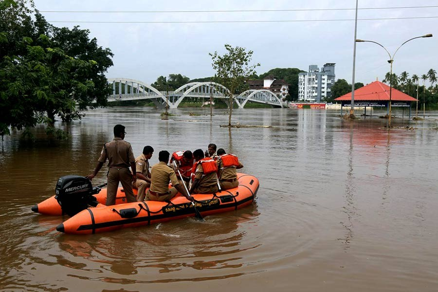 Rescue personnel patrolling the flooded waters on the banks of Periyar River after the opening of Idamalayar and Cheruthoni dam shutters following heavy rains, on the outskirts of Kochi on Friday. -Reuters Photo