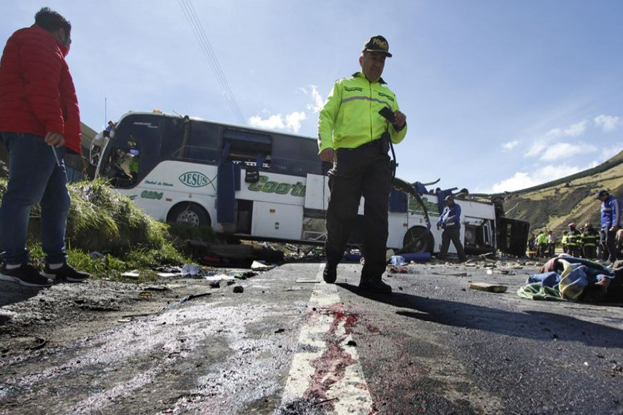 A police officer walks past a Colombian-registered bus that crashed while traveling to Quito, Ecuador on Tuesday — AP photo