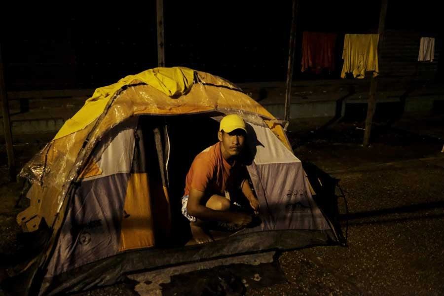 Venezuelan man is pictured at the entrance of his, tent set up along the street, as he waits to show his passport or identity card next day at the Pacaraima border control, Roraima state, Brazil August 8, 2018. Reuters