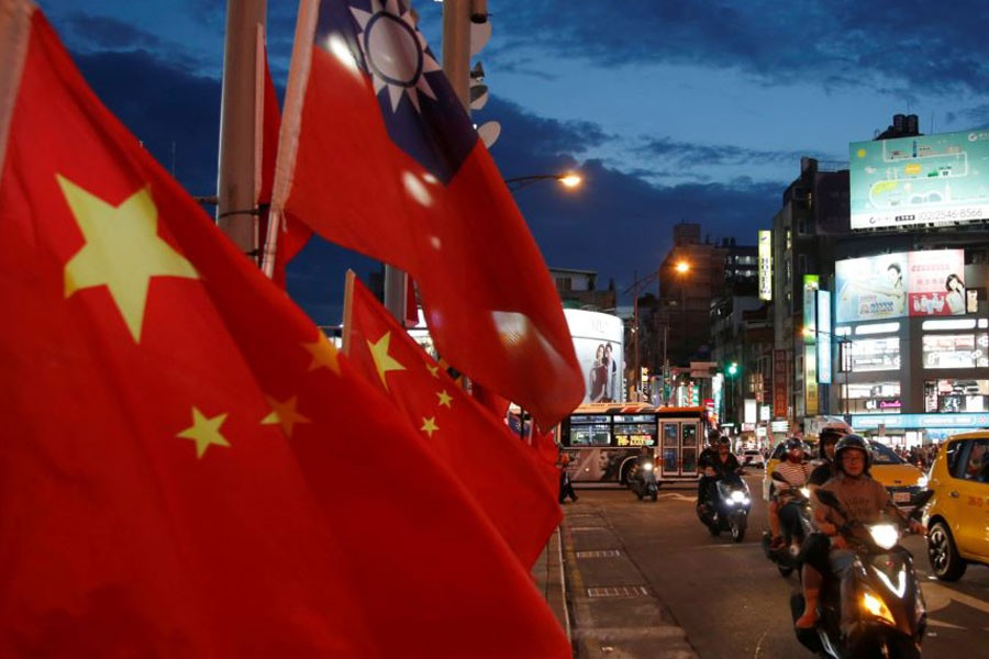 Flags of China and Taiwan flutter next to each other during a rally calling for peaceful reunification, days before the inauguration ceremony of President Tsai Ing-wen, in Taipei, Taiwan, May 14, 2016 – Reuters file photo