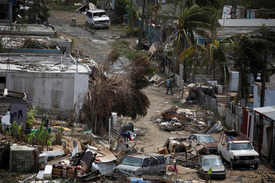 A man carrying a water container walks next to damaged houses after the area was hit by Hurricane Maria in Canovanas, Puerto Rico, September 26, 2017. Reuters/Files