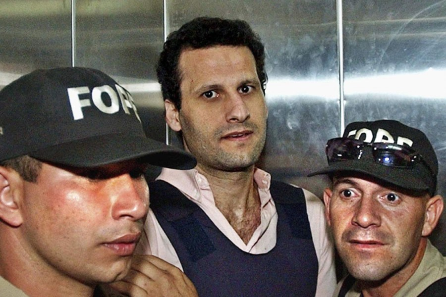 Lebanese citizen Assad Ahmad Barakat, who was then facing tax evasion charges, is escorted by police to a courthouse in Asuncion, Paraguay, on November 17, 2003 - AP file Photo
