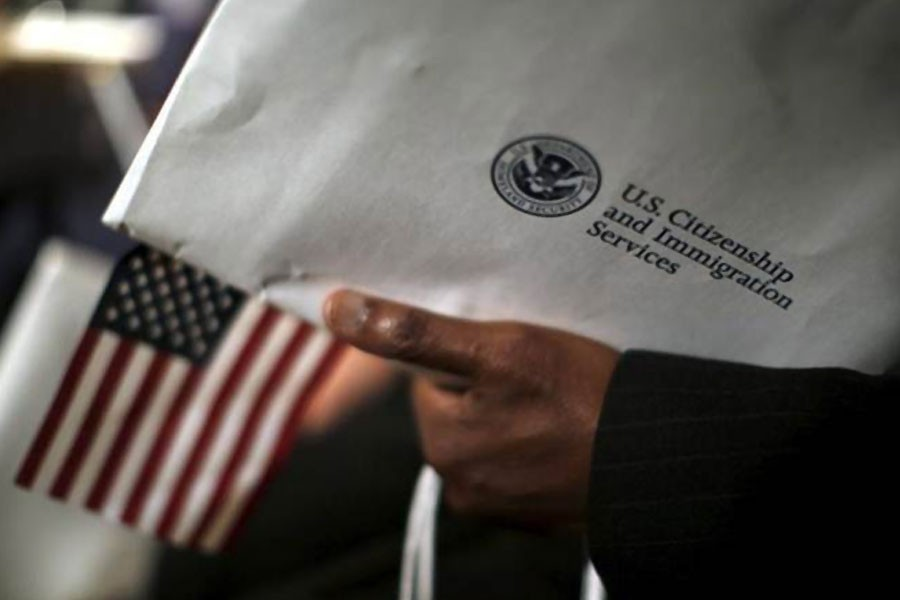 A man holds an envelope from the US Citizenship and Immigrations Service during a naturalisation ceremony at the National Archives Museum in Washington December 15, 2015 – Reuters
